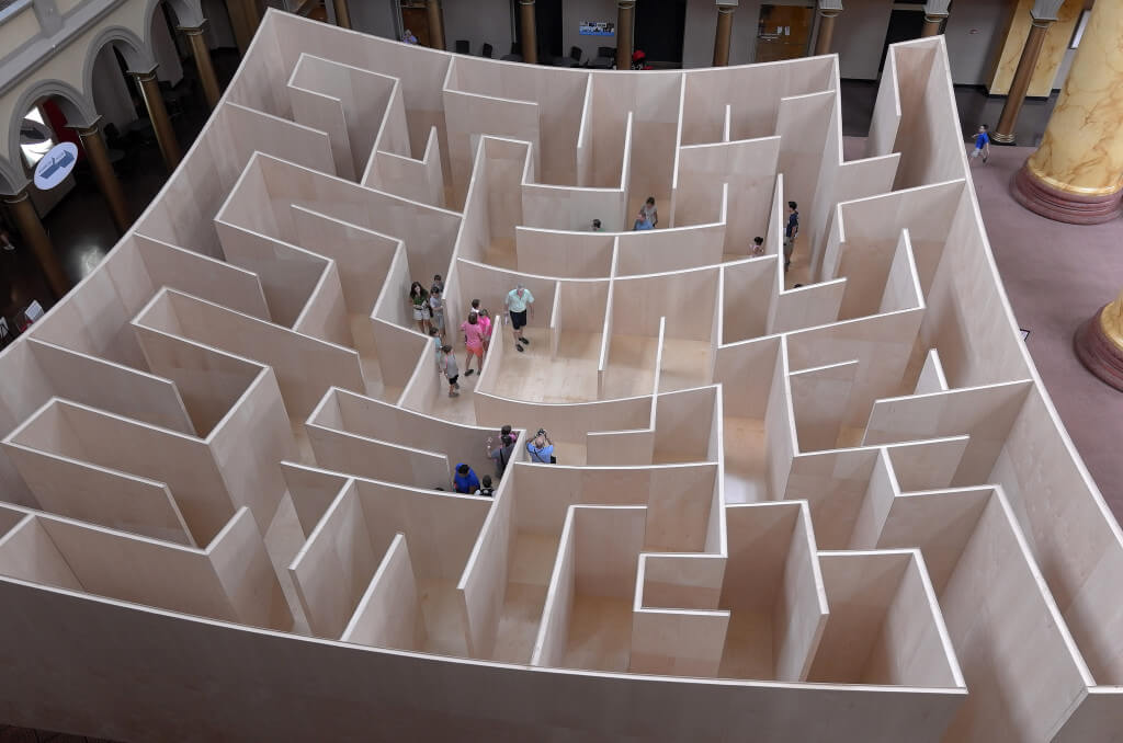 People walking through wooden maze indoors